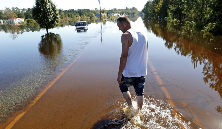 Elmer McDonald makes his way along a flooded street as he returns to his mobile home for the first time to inspect damage caused by floodwaters associated with Hurricane Matthew in Lumberton, N.C., on Thursday, Oct. 13, 2016. McDonald and about 1,200 other Lumberton residents had to be evacuated by boat or plucked from their roofs by helicopters as the river crested. (AP Photo/Brian Blanco)