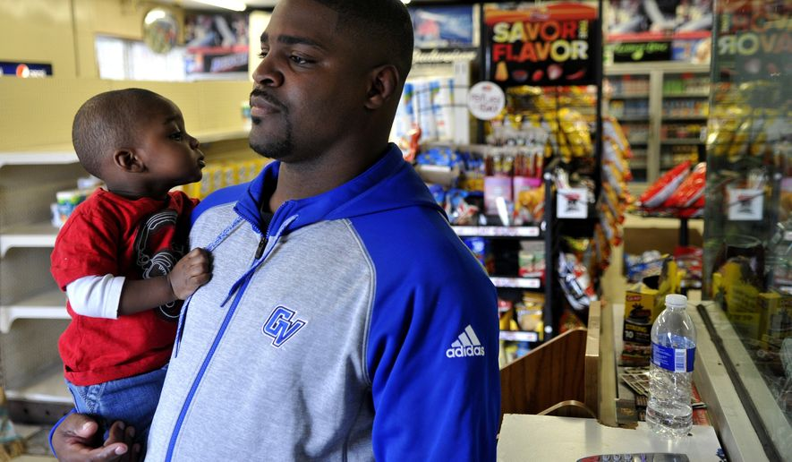 ADVANCED FOR RELEASE SUNDAY, OCTOBER 16, 2016 Flint native and professional boxer Dion Savage Jr. stands in the doorway of his business with his one-year-old son Wali Savage on Tuesday, Oct. 4, 2016 at Dion's Party Store in Flint. After closing in November of 2014, Savage invested money to reopen the family-run business on March 2, 2016. (Tegan Johnston/The Flint Journal, MLive.com via AP)