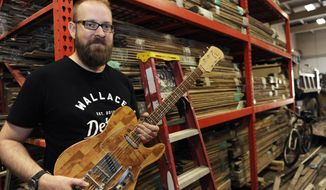 ADVANCE FOR USE MONDAY, OCT. 17 - In this Sept. 20, 2016 photo, Mark Wallace, CEO of Wallace Detroit Guitars, holds a guitar in Detroit. Wallace, who started the company in 2014, uses reclaimed wood from Detroit homes and buildings to make custom-made guitars he sells online. (ClarenceTabb Jr./Detroit News via AP)