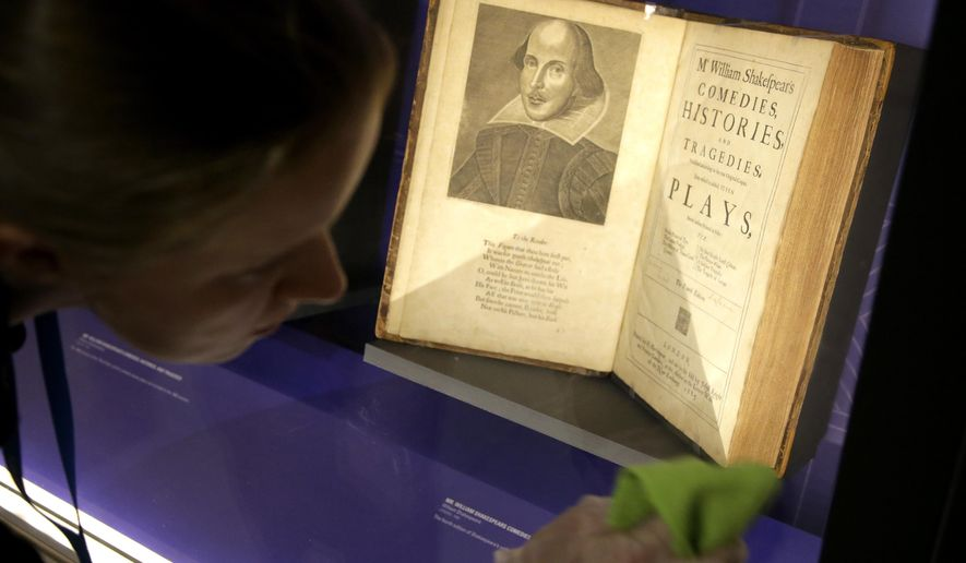 "In this Tuesday, Oct. 11, 2016 photo book conservator Lauren Schott polishes a case containing 17th century editions of plays attributed to William Shakespeare in an exhibit called ""Shakespeare Unauthorized"" at the Boston Public Library, in Boston. The public is to get a rare glimpse of first and early editions of some of Shakespeare's most beloved plays, including ""A Midsummer Night's Dream,"" Hamlet"" and ""The Merchant of Venice"" in the exhibit which opens Friday, Oct. 14 and is to run through March 31 at the library. (AP Photo/Steven Senne)"