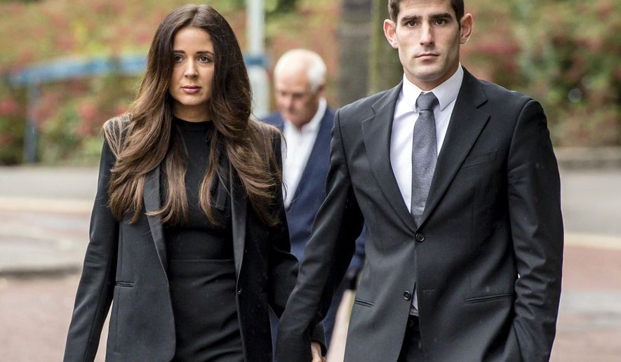 Football player Ched Evans, right, and his partner Natasha Massey arrive at Cardiff Crown Court, in Cardiff, Friday, Oct. 14, 2016,  where he is on trial accused of raping a woman in 2011. A former English Premier League footballer has been found not guilty of rape following a retrial, ending a five-year fight to clear his name. (Ben Birchall/PA via AP)