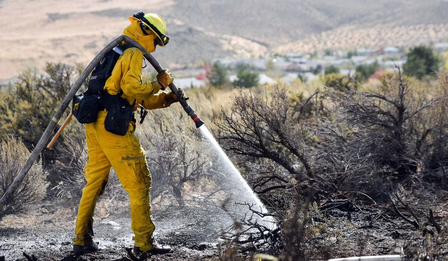 A firefighter hoses down the area on Mount Rose Highway and Edmonton Drive, Friday, Oct. 14, 2016 in Reno, Nev.. A wind-whipped wildfire raged out of control Friday in northern Nevada, destroying more than a dozen homes, forcing evacuations, closing roads and schools, and triggering power outages, officials said.(Mike Higdon/The Reno Gazette-Journal via AP)