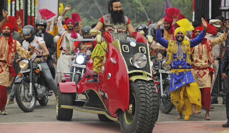 """In this Wednesday, Oct. 5, 2016 photo, Indian spiritual guru, who calls himself Saint Dr. Gurmeet Ram Rahim Singh Ji Insan, arrives for a press conference ahead of the release of his new film """"MSG, The Warrior Lion Heart,"""" in New Delhi, India. The leader of the quasi-religious sect has launched a film franchise in which he stars as Messenger of God, or MSG for short, with divine powers to save the world. He claims to have 50 million followers and runs a spiritual empire that promotes vegetarianism and campaigns against drug addiction. With a guaranteed audience among his followers, Insan said he's had little trouble getting his films released commercially in cinemas. (AP Photo/Tsering Topgyal)"""