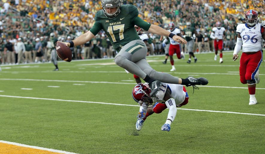 Baylor quarterback Seth Russell (17) leaps but is hit by Kansas linebacker Mike Lee (11) before entering the end zone for a touchdown after a short run in the first half of an NCAA college football game, Saturday, Oct. 15, 2016, in Waco, Texas. (AP Photo/Tony Gutierrez)