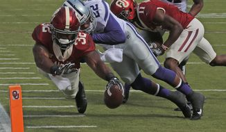 Oklahoma running back Samaje Perine (32) dives into the end zone in front of Kansas State defensive back Dante Barnett (22) for a touchdown in the first quarter of an NCAA college football game in Norman, Okla., Saturday, Oct. 15, 2016. (AP Photo/Sue Ogrocki)