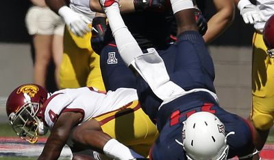 Southern California defensive back Chris Hawkins (4) upends Arizona quarterback Khalil Tate (14) during the first half of an NCAA college football game, Saturday, Oct. 15, 2016, in Tucson, Ariz. (AP Photo/Rick Scuteri)