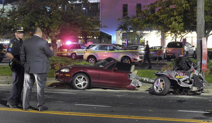 Police survey the wreckage of a Mazda Miata that was split in half after a collision with a Mercedes-Benz in Rockville Centre, on New York's Long Island, Friday Oct. 14, 2016. Police said nobody suffered life-threatening injuries. The driver of the Mazda suffered internal injuries. The driver of the Mercedes-Benz and his 25-year-old female passenger had to be extricated from their vehicle. (Paul Mazza/Newsday via AP