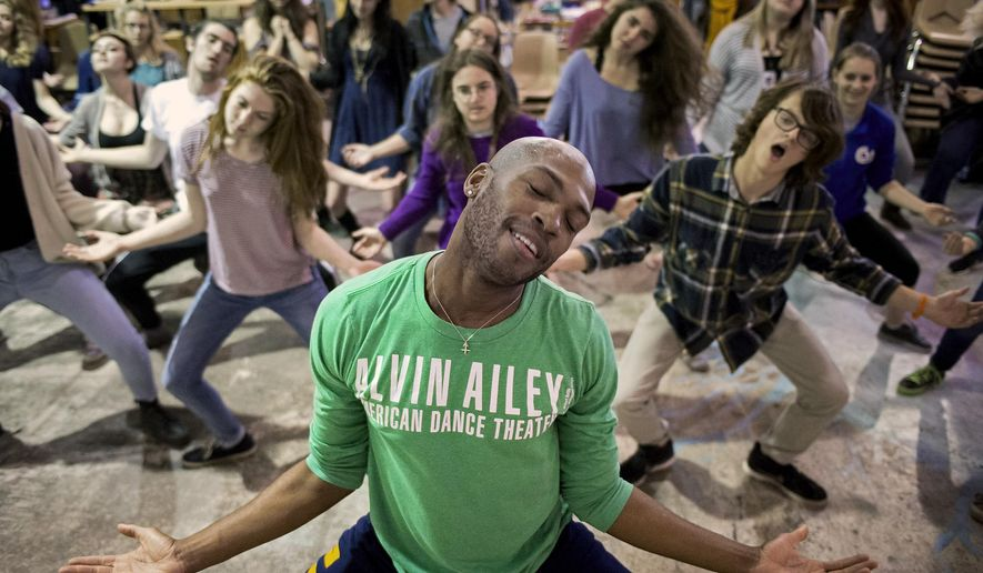 In this Tuesday, April 7, 2015 photo, dancer Antonio Douthit, front, of the Alvin Ailey American Dance Theater teaches a group of high school students a sampling of modern dance choreography during class at the site of the Lincoln Public Schools Arts and Humanities Focus Program, in Lincoln, Neb. (Kristin Streff/The Journal-Star via AP)