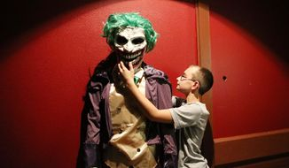 ADVANCE FOR USE SATURDAY, OCT. 15 - In this Thursday, Oct. 6, 2016 photo, Mason Jelken places the head on an animatronic monster as West Middle School students set up for a haunted house on Jackson Street in Sioux City, Iowa. (Jim Lee/Sioux City Journal via AP)