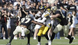 Iowa's Akrum Wadley (25) runs against Purdue's Navon Mosley (27) and Jimmy Herman during the first half of an NCAA college football game, Saturday, Oct. 15, 2016, in West Lafayette, Ind. (AP Photo/Darron Cummings)
