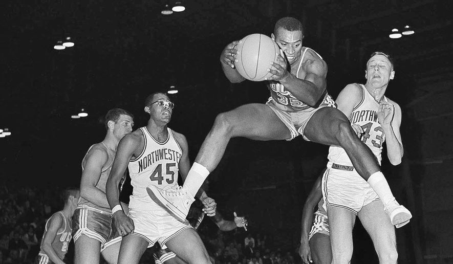 FILE - In this Dec. 20, 1962 file photo, UCLA's Fred Slaughter (35) leaps in the air to grab a rebound during the first period of a college basketball game against Northwestern University in Evanston, Ill. Slaughter, who helped UCLA win its first-ever NCAA basketball championship as a senior under coach John Wooden in 1964, has died Oct. 6 at his home in Santa Monica, the school announced Saturday, Oct. 15, 2016. No cause of death was given. He was 74.  (AP Photo/Larry Stoddard, File)