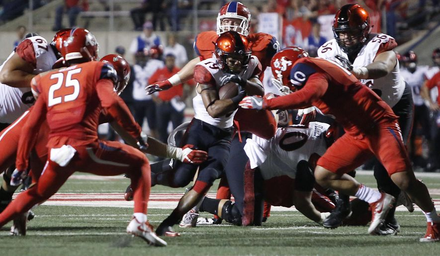 San Diego State's Donnel Pumphrey runs past Fresno State's Nela Otukolo, right, during the first half of an NCAA college football game in Fresno, Calif., Friday, Oct. 14, 2016. (AP Photo/Gary Kazanjian)