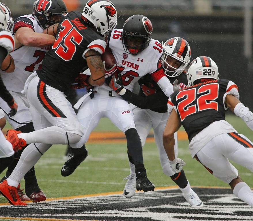 Utah's Cory Butler-Boyd (16) tries to push past Oregon State's Caleb Saulo (35) and Xavier Crawford (12) during the first half of an NCAA college football game in Corvallis, Ore., on Saturday, Oct. 15, 2016. (AP Photo/Timothy J. Gonzalez)