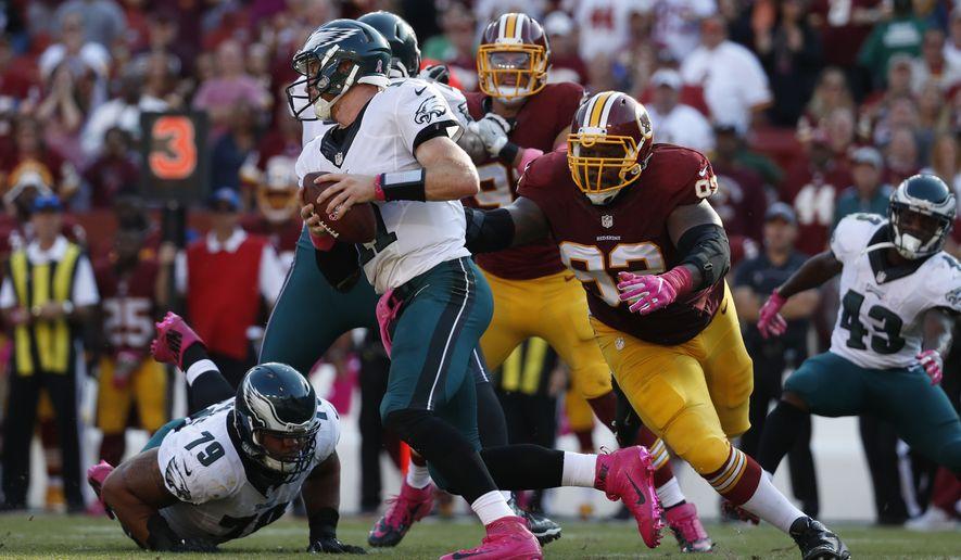 Philadelphia Eagles quarterback Carson Wentz, center, tries to outrun Washington Redskins defensive end Chris Baker (92) in the second half of an NFL football game, Sunday, Oct. 16, 2016, in Landover, Md. (AP Photo/Alex Brandon)