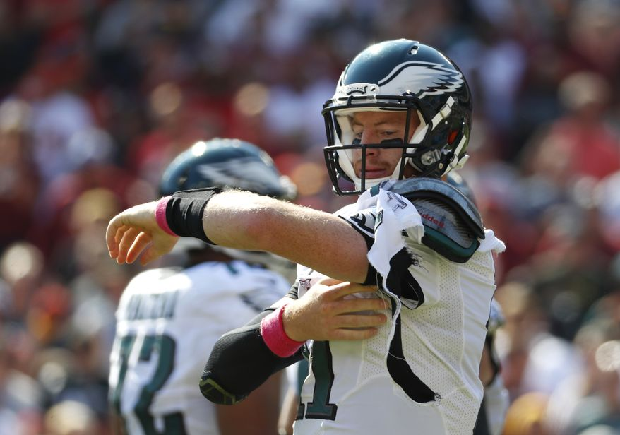 Philadelphia Eagles quarterback Carson Wentz tries to fix his jersey after it was torn in the first half of an NFL football game against the Washington Redskins, Sunday, Oct. 16, 2016, in Landover, Md. (AP Photo/Alex Brandon)