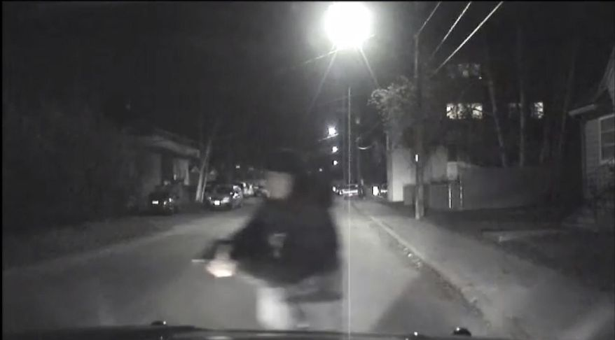 An image from video provided by the Fairbanks Police Department shows shows the suspect police believe abandoned a police car he stole after he shot an officer in Fairbanks, Ak., early Sunday, Oct. 16, 2016. An Alaska police officer was seriously injured in the early morning shooting, according to the Fairbanks police department. The Fairbanks News-Miner reports the officer was flown to Anchorage for treatment. Police are still searching for the shooter.  (Fairbanks Police Department via AP)