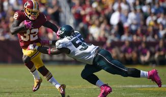 Washington Redskins running back Rob Kelley, left, pushes away Philadelphia Eagles defensive end Brandon Graham as he rushes the ball in the first half of an NFL football game, Sunday, Oct. 16, 2016, in Landover, Md. (AP Photo/Nick Wass)