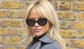 "FILE - In this Wednesday, Oct. 12, 2016 file photo, Pamela Anderson poses for photographers, during a photo call, in London. Former ""Baywatch"" star Pamela Anderson has brought WikiLeaks chief Julian Assange a vegan meal and expressed concern for his health. She told Britain's Press Association on Sunday that she had brought Assange ""a nice vegan lunch and some vegan snacks"" the day before, it was reported on Sunday, Oct. 16, 2016. (Photo by Grant Pollard/Invision/AP, File)"