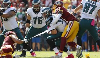 Philadelphia Eagles quarterback Carson Wentz's jersey tears as he is tackled by Washington Redskins outside linebacker Ryan Kerrigan, left, and free safety Will Blackmon in the first half of an NFL football game, Sunday, Oct. 16, 2016, in Landover, Md. (AP Photo/Alex Brandon)