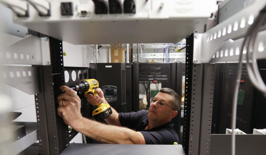 In this Thursday, Oct. 13, 2016 photo, Robert Mohan installs new radio equipment at the 911 dispatch center at the Rensselaer County Public Safety Building in Troy, N.Y. New York trails other states in modernizing its 911 systems to handle greater cellphone use, in part because lawmakers routinely divert money intended for that purpose and use it to plug holes in the state budget. (AP Photo/Mike Groll)