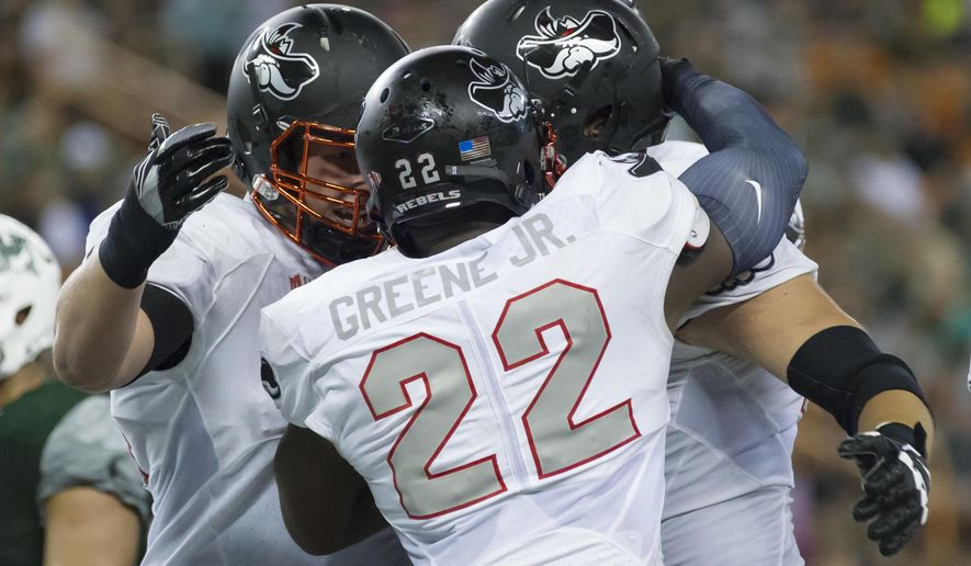 UNLV running back David Greene (22) is congratulated by teammates after scoring a touchdown late in the second quarter of an NCAA college football game against Hawaii, Saturday, Oct. 15, 2016, in Honolulu. (AP Photo/Eugene Tanner)