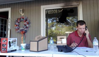 Blake Halsey, a 21-year-old college student and volunteer at the Orange County GOP office, takes a phone call from someone offering to volunteer on Monday, a day after authorities say someone firebombed the campaign office. (Associated Press)