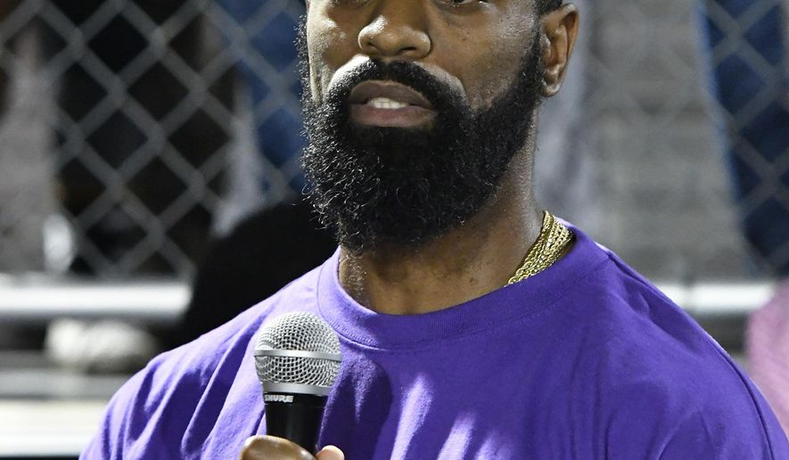Former Olympian Tyson Gay speaks to the mourners gathered in memory of his daughter Trinity at Lafayette High School, Monday, Oct. 17, 2016, in Lexington, Ky. Several thousand people, including Tyson Gay, turned out Monday night for a candlelight vigil in Kentucky to honor Gay's 15-year-old daughter, who was fatally shot over the weekend. (AP Photo/Timothy D. Easley)