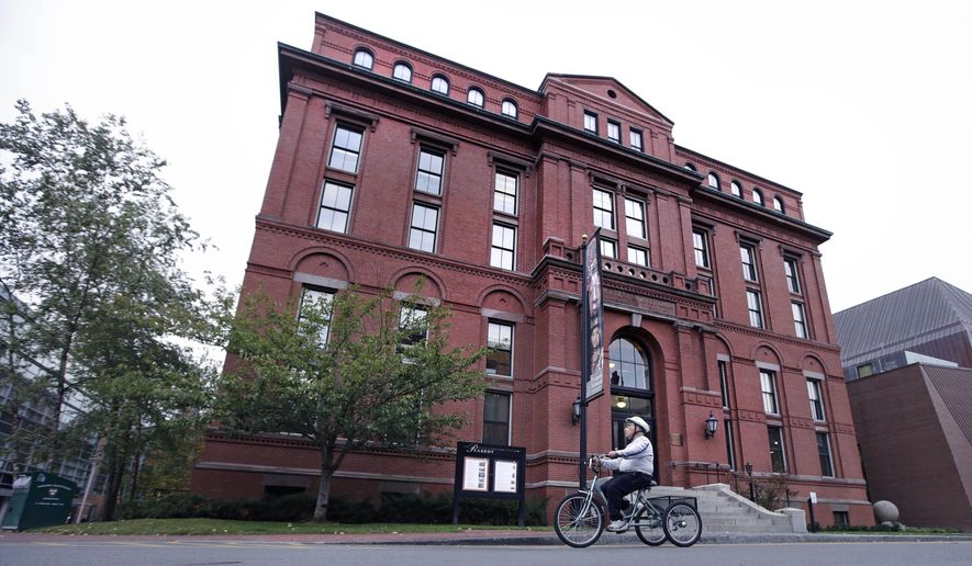 A cyclist rolls past the Peabody Museum of Archaeology & Ethnology at Harvard University in Cambridge, Mass., Thursday, Oct. 13, 2016. The Peabody, one of the oldest and largest museums in the world focused on the study of societies and cultures, turns 150 years old this month. (AP Photo/Charles Krupa)