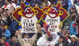 """FILE - In this April 8, 2002, file photo, fans hold up Chief Wahoo signs as they celebrate the Cleveland Indians' win over the Minnesota Twins, in Cleveland, Ohio. A Toronto court will hear arguments Monday, Oct. 17, 2016 on an attempt to bar the Cleveland Indians from using their team name and """"Chief Wahoo"""" logo in Ontario. (AP Photo/Tony Dejak, File)"""