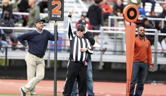 Unbiversity of Michigan NCAA college football head coach Jim Harbaugh, left,  holds the down marker on the sideline during the game between El Cerrito and St. Mary's High at St. Mary's High School in Albany, Calif., on Saturday, Oct. 15, 2016. Harbaugh spent Michigan's weekend off working the chains at a high school football game in California. (Ray Chavez/Bay Area News Group)