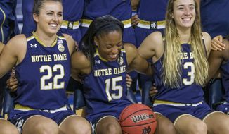 Lindsay Allen (15) laughs as she poses for team photos between teammates Erin Boley (22) and Marina Mabrey (3) during Notre Dame's NCAA basketball media day, Monday, Oct. 17, 2016, inside the Purcell Pavilion at Notre Dame in South Bend, Ind. (Robert Franklin/South Bend Tribune via AP)