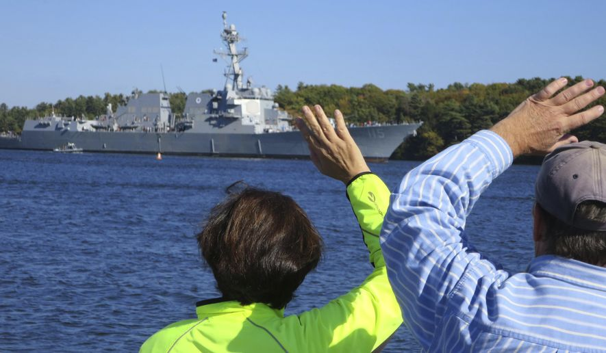 Spectators wave as the future USS Rafael Peralta leaves Bath Iron Works for builder trials, Monday, Oct. 17, 2016, in Bath, Maine. Six Navy destroyers, including Peralta, are currently under construction at Bath Iron Works and another three are under contract, but shipbuilders are worried about the future after losing an important Coast Guard contract worth $10 billion. (AP Photo/David Sharp)