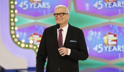 """In this image released by CBS, host Drew Carey appears on the set of """"The Price is Right."""" On the episode airing Monday, Oct. 17, 2016, a trio of contestants spun $1 on the game show's famous wheel. The three contestants each landed on different combinations of $1 in a pair of spins during one of the show's showcase showdowns. Carey pumped his fist in the air after the contestants achieved the first three-way tie in the show's history. (Monty Brinton/CBS via AP)"""