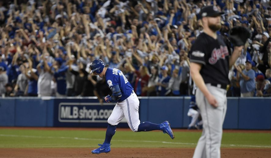 Toronto Blue Jays third baseman Josh Donaldson (20) reacts as he rounds the bases on a solo home run against Cleveland Indians pitcher Corey Kluber (right) during third inning, game four American League Championship Series baseball action in Toronto on Tuesday, Oct. 18, 2016. (Nathan Denette/The Canadian Press via AP)