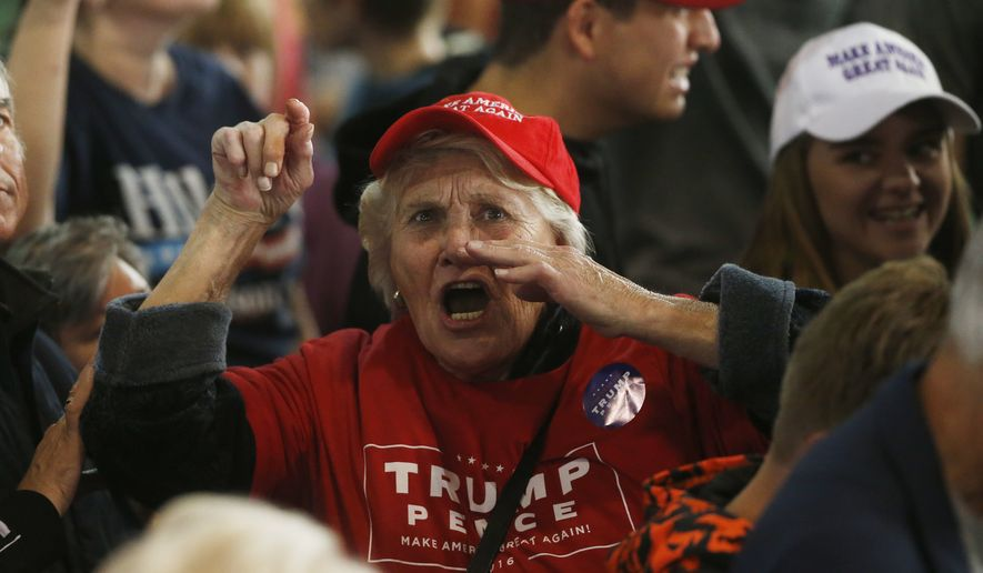 A supporter of Republican presidential candidate Donald Trump berates the media as she leaves a campaign rally for Trump, Tuesday, Oct. 18, 2016, in Colorado Springs, Colo. (AP Photo/David Zalubowski)