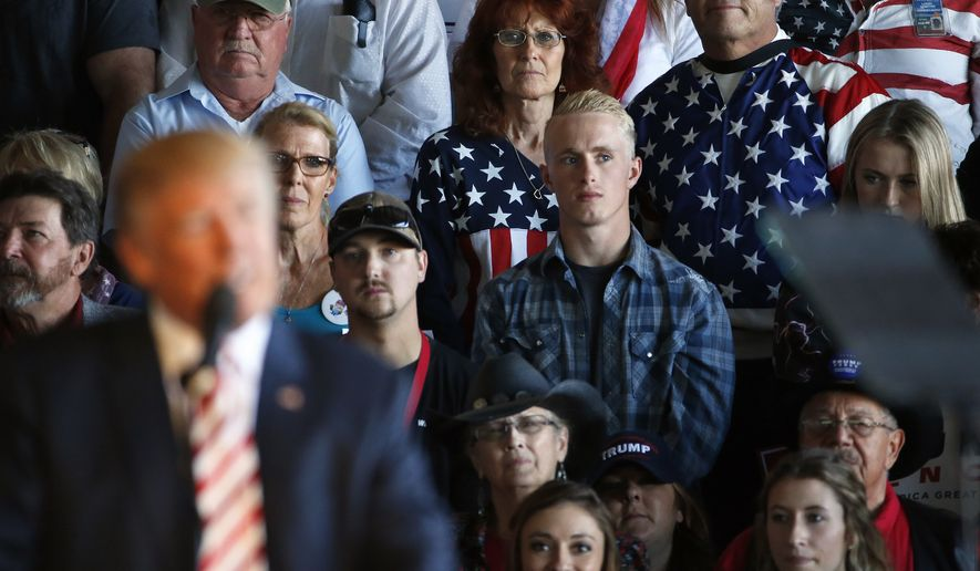 Supporters of Republican presidential candidate Donald Trump listen as Trump, at left, speaks at a campaign rally, Tuesday, Oct. 18, 2016, in Grand Junction, Colo. (AP Photo/ Brennan Linsley)