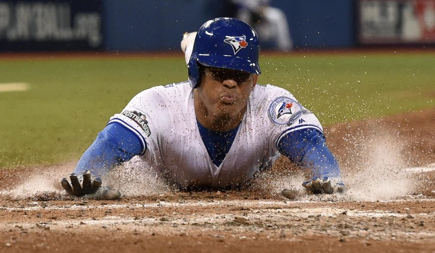 Toronto Blue Jays' Ezequiel Carrera scores from third on a groundout by Ryan Goins during the fifth inning in Game 3 of baseball's American League Championship Series against the Cleveland Indians in Toronto, Monday, Oct. 17, 2016. (Frank Gunn/The Canadian Press via AP)