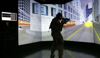 A soldier stands in a virtual reality lab wearing a headset to measure his cognitive responses under stress, Tuesday, Oct. 18, 2016, at the Center for Applied Brain and Cognitive Sciences in Medford, Mass. The Center was jointly founded by the Army's Natick Soldier Research, Development and Engineering Center and Tufts University's School of Engineering. (AP Photo/Elise Amendola)