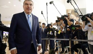 International Olympic Committee President Thomas Bach, left, arrives at Haneda Airport in Tokyo Tuesday, Oct. 18, 2016. Bach is set to meet Tokyo's governor pushing for changes to some of the planned venues for the 2020 Games. (Hiroki Yamauchi/Kyodo News via AP)