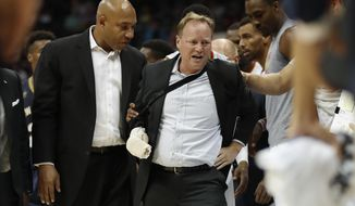 Atlanta Hawks coach Mike Budenholzer, center, is helped to his feet by assistant coach Darvin Ham, left, after he was run over along the sideline during the first half of the team's preseason NBA basketball game against the New Orleans Pelicans Tuesday, Oct. 18, 2016, in Atlanta. Budenholzer, who was already nursing an injured hand, left the game. (AP Photo/John Bazemore)