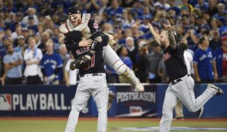 Cleveland Indians' Cody Allen (37), Roberto Perez (55) and Mike Napoli (26) celebrate the team's 3-0 victory over the Toronto Blue Jays during Game 5 of the baseball American League Championship Series, in Toronto on Wednesday, Oct. 19, 2016. (Nathan Denette/The Canadian Press via AP)