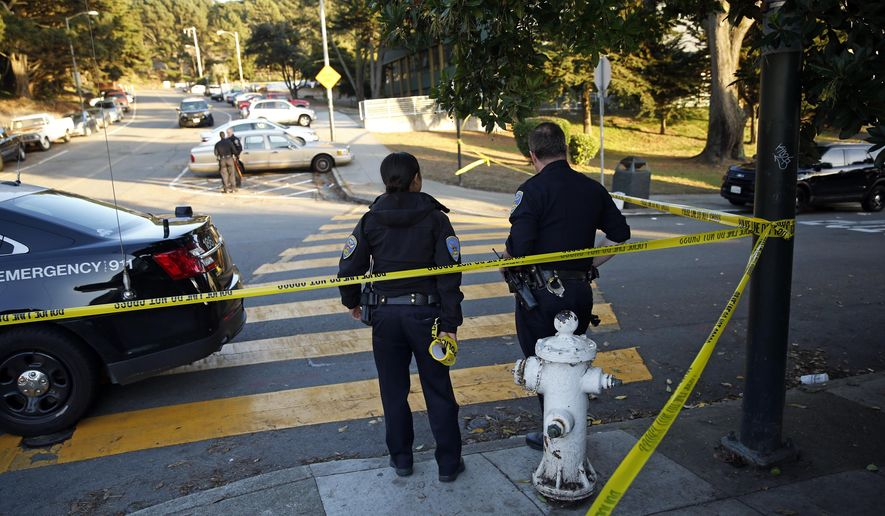 San Francisco Police stand at the site of a shooting outside the June Jordan School for Equity and City Arts and Technology High School, which share a campus, in San Francisco, Calif., Tuesday, Oct. 18, 2016. Several teenage students were shot in the shared parking lot of the two San Francisco high schools Tuesday, and one of the students is in critical condition, authorities said. (Scott Strazzante/San Francisco Chronicle via AP)