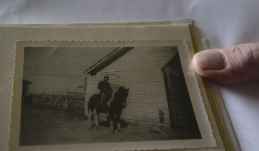 ADVANCE FOR WEEKEND EDITIONS - In this Oct. 4, 2016, photo, Terry Roedel shows an old photograph of himself training his horse in front of the original barn at his family farm in Caldwell, Utah. (Chris Bronson/The Idaho Press-Tribune via AP)