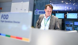An employee stands in the control center  of the European Space Agency (ESA) in Darmstadt, Germany, Wednesday Oct. 19,  2016.  ESA and its Russian partner Roskosmos hope for the first successful landing on Mars. Their landing modul Schiaparelli will enter the martian atmosphere at an altitude of about 121 km and a speed of nearly 21 000 km/h. Less than six minutes later it will have landed on Mars. The probe will take images of Mars and conduct scientific measurements on the surface, but its main purpose is to test technology for a future European Mars rover.  Schiaparelli's mother ship ,TGO, will remain in orbit to analyze gases in the Martian atmosphere to help answer whether there is or was life on Mars,  (Uwe Anspach/dpa via AP)