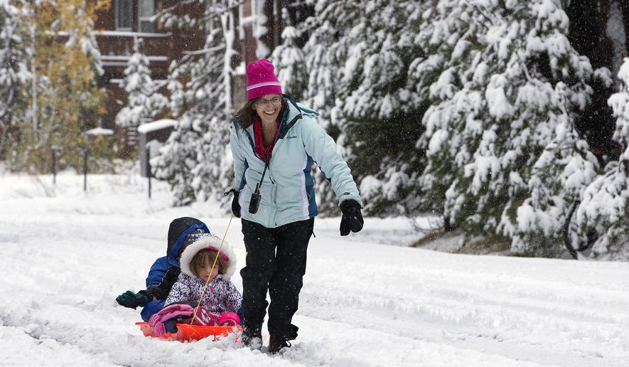 Debbie Kahn, right, pulls her son, Eli, 7, left, and daughter, Talia, 2, McLaughlin through the snow at Serene Lakes, Monday, Oct. 17, 2016, near Soda Springs, Calif. A weekend storm brought rain to Northern California and snow to the Sierra Nevada. (AP Photo/Rich Pedroncelli)