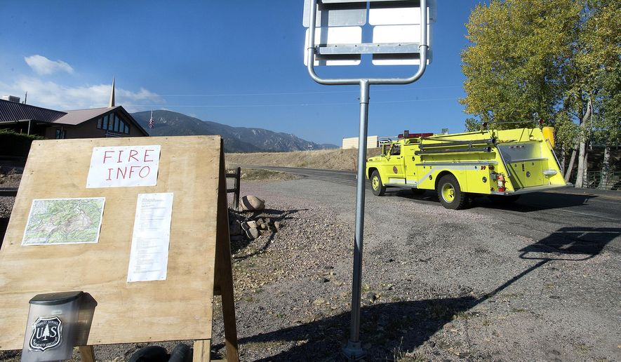 A fire vehicle on the way to the Junkins Fire drives through the point where Colorado Highway 96 is closed at Wetmore, Colo. on Wednesday, Oct. 19, 2016. A wooden sign board at left gives fire information to residents, some of whom are under evacuation since Monday morning when the fire began between Wetmore and Westcliffe in Custer County. (Chris McLean/The Pueblo Chieftain via AP)