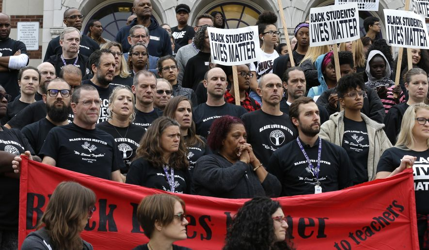 """Teachers wearing """"Black Lives Matter"""" t-shirts join with students at a rally Wednesday, Oct. 19, 2016 at Garfield High School in Seattle. Teachers, students and parents across Seattle public schools wore the shirts Wednesday to promote racial equity in schools. (AP Photo/Ted S. Warren)"""