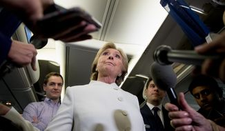 Democratic presidential candidate Hillary Clinton, center, accompanied by Campaign Manager Robby Mook, left, and traveling press secretary Nick Merrill, right, takes a question from a member of the media aboard her campaign plane at McCarran International Airport in Las Vegas, Wednesday, Oct. 19, 2016, following the third presidential debate. (AP Photo/Andrew Harnik)