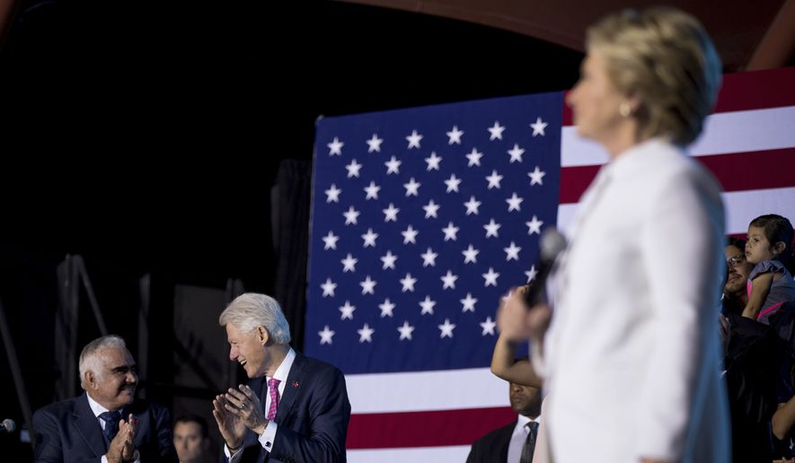 Singer Vicente Fernandez, left, and former President Bill Clinton, second from left, applaud together as Democratic presidential candidate Hillary Clinton speaks at a debate watch party at Craig Ranch Regional Amphitheater in North Las Vegas, Wednesday, Oct. 19, 2016, following the third presidential debate. (AP Photo/Andrew Harnik)