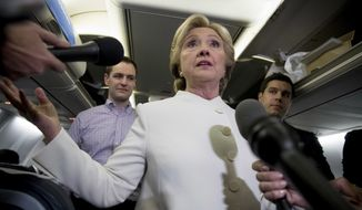 Democratic presidential candidate Hillary Clinton, center, accompanied by Campaign Manager Robby Mook, left, and traveling press secretary Nick Merrill, right, speaks with members of the media aboard her campaign plane at McCarran International Airport in Las Vegas, Wednesday, Oct. 19, 2016, following the third presidential debate. (AP Photo/Andrew Harnik) ** FILE **